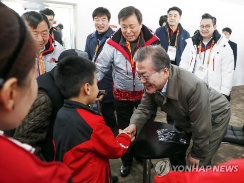 3月14日,在江原道平昌,韩国总统文在寅与韩国选手家属亲切交谈。(韩联社)