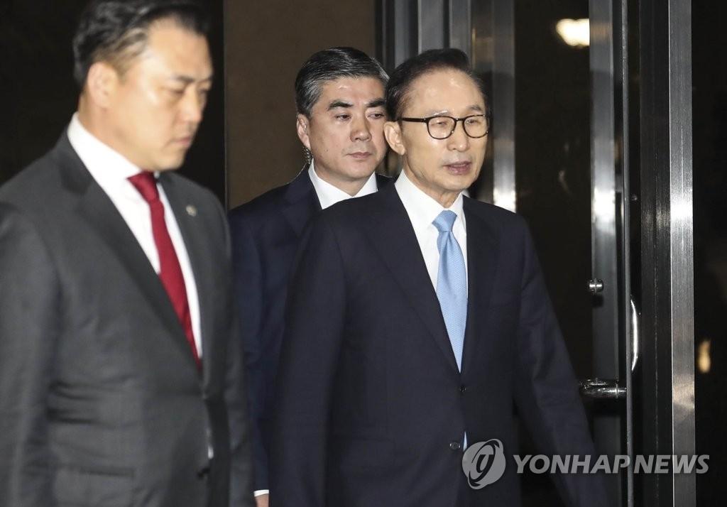 3月15日,韩国前总统李明博走出检察厅。(韩联社)