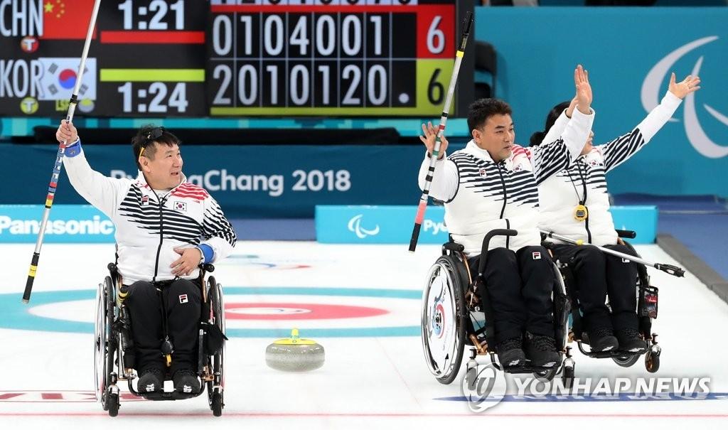 3月15日,在江陵冰球中心,韩国队在2018平昌冬残奥会轮椅冰壶小组循环赛中以7:6战胜中国队。图为韩国选手获胜后向观众挥手致意。(韩联社)