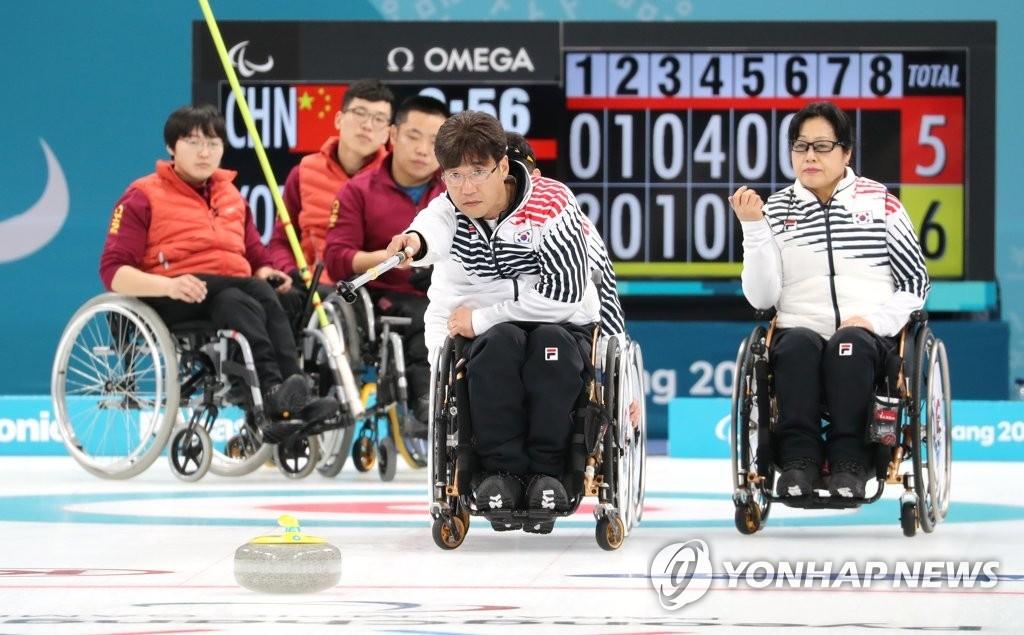 3月15日,在江陵冰球中心,韩国队选手徐淳锡(音)在2018平昌冬残奥会轮椅冰壶小组循环赛中投掷冰壶。(韩联社)