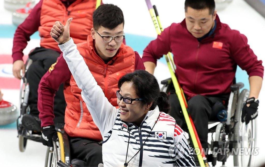 3月15日,在江陵冰球中心,韩国队在2018平昌冬残奥会轮椅冰壶小组循环赛中以7:6战胜中国队。图为韩国选手方敏子(音)获胜后向观众挥手致意。(韩联社)