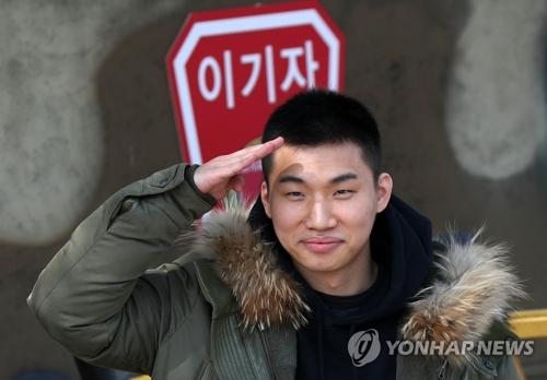 3月13日下午,在江原道华川郡,BIGBANG成员大成前往陆军第27师新兵教育队报到并向记者和粉丝敬礼致意。(韩联社)