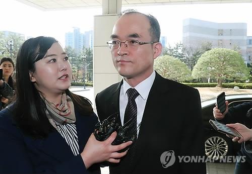 3月16日上午,在韩国大检察厅,文武一(右)在上班前答记者问。(韩联社)