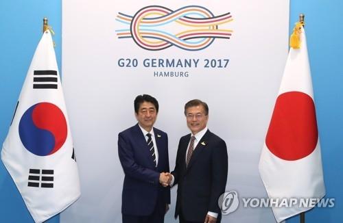 资料图片:当地时间2017年7月7日,在德国汉堡,韩国总统文在寅(左)与日本首相安倍晋三在会谈前握手合影。(韩联社)