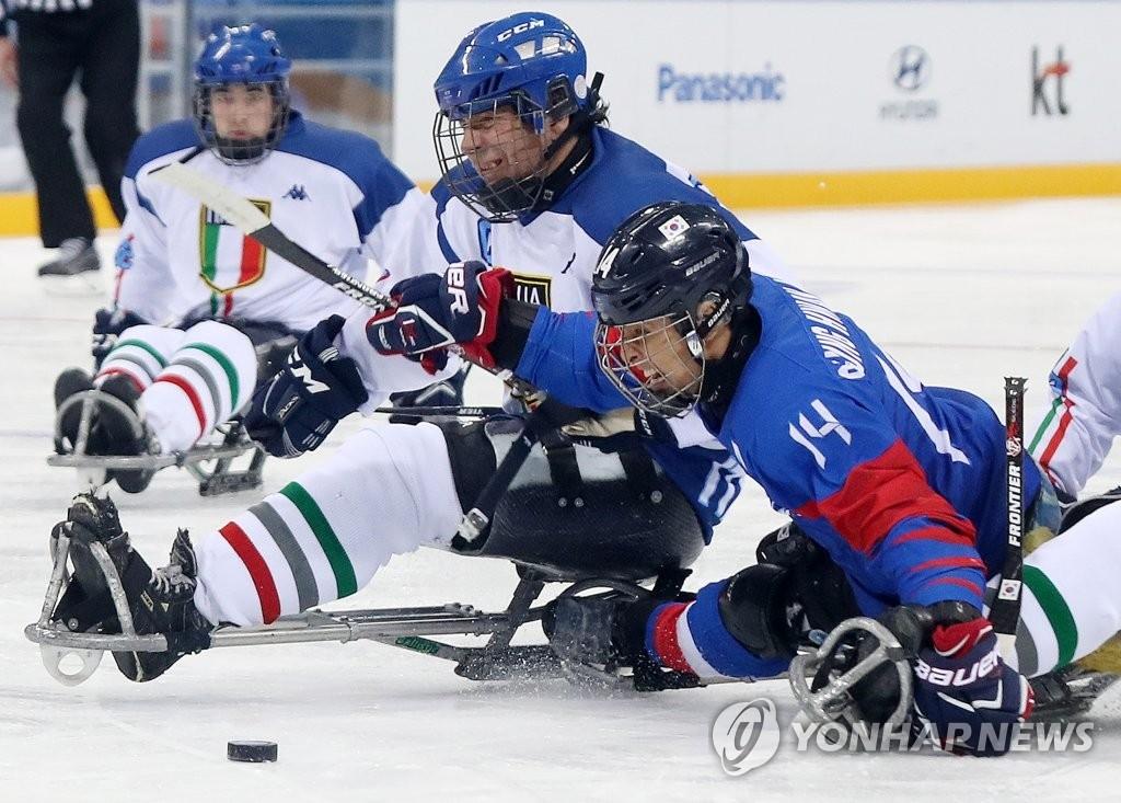 3月17日,在江原道江陵冰球中心举行的冬残奥冰球铜牌争夺赛上,韩国队和意大利队正在全力投入比赛。蓝色上衣为韩国队。(韩联社)