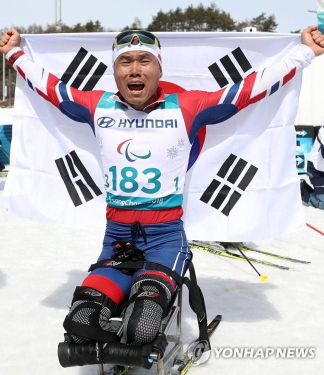 3月17日,在江原道平昌阿尔卑西亚冬季两项中心,韩国越野滑雪运动员申义贤举国旗欢呼庆祝夺金。(韩联社)