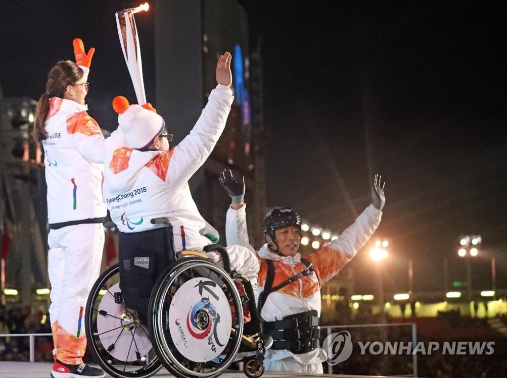 3月9日晚,在平昌奥林匹克体育场,韩国女子冰壶运动员金恩静(左)与残疾人运动员共举圣火向观众挥手致意。(韩联社)