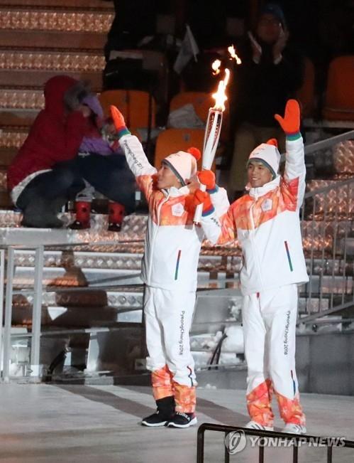 资料图片:3月9日下午,在平昌奥林匹克体育场举行的2018平昌冬残奥会开幕式上,韩朝火炬手共同高举冬残奥会圣火向观众招手致意。左为韩国越野滑雪运动员崔宝奎,右为朝鲜北欧滑雪运动员马有喆(人名均为音译)。(韩联社)