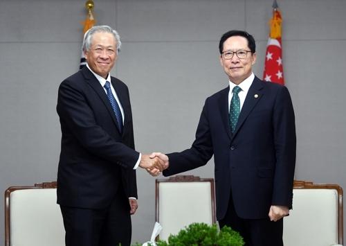 韩国防长宋永武(右)和新加坡防长黄永宏(韩联社)