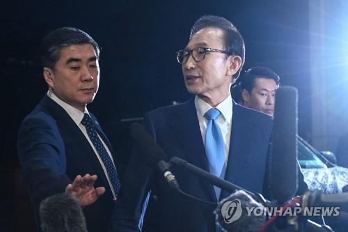 3月15日上午,在首尔中央地方检察厅,李明博在接受传讯后向检方人员道别。(韩联社)