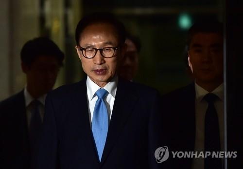 资料图片:3月15日,李明博在接受调查后走出首尔中央地方检察厅。(韩联社)