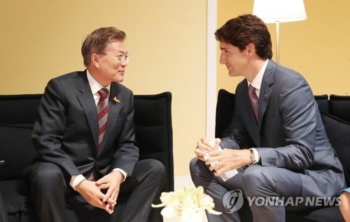 资料图片:当地时间2017年7月8日,在德国汉堡国际会展中心,韩国总统文在寅(左)与加拿大总理特鲁多举行会晤。(韩联社/青瓦台提供)