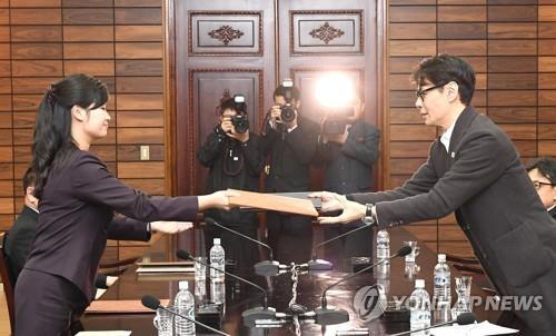 3月20日上午,在板门店,尹相和玄松月在韩朝工作会谈上交换双方商定的联合新闻稿。(韩联社)