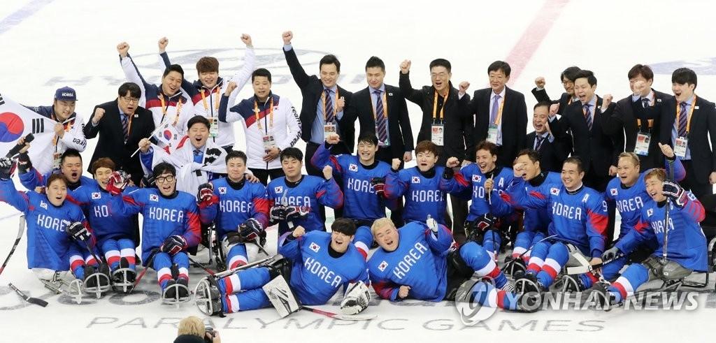 资料图片:3月17日,在江原道江陵冰球中心,韩国男子冰球队在平昌冬残奥会残疾人冰球铜牌争夺赛上战胜意大利,摘下铜牌。图为队员们合影庆祝。(韩联社)