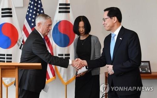 资料图片:韩国防长宋永武(右)同美国国防部长马蒂斯握手。(韩联社)