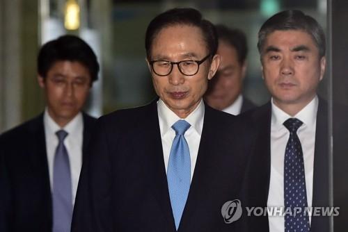 资料图片:3月15日上午,在首尔中央地方检察厅,李明博在接受讯问后回家。(韩联社)