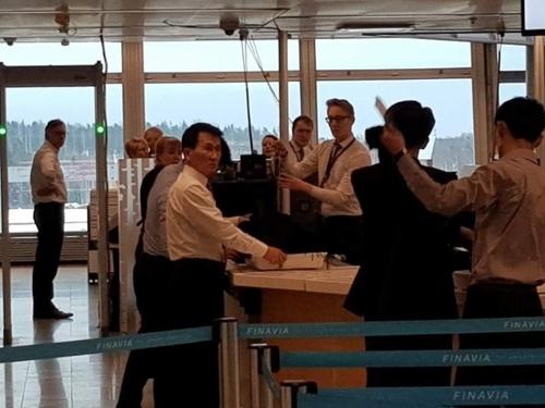 朝鲜外务省北美局副局长崔强一(左)在芬兰万塔机场接受安检准备离境。(韩联社)