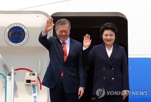 3月22日下午,在河内机场,韩国总统文在寅(左)和夫人金正淑向越南接机人员招手。(韩联社)