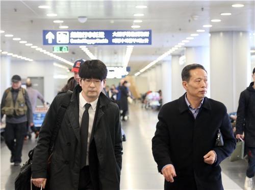 3月22日下午,在北京首都机场,韩国青瓦台高级行政官卓贤民(左)在朝方工作人员的指引下前往搭乘高丽航空JS252航班。(韩联社)