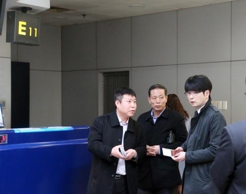 3月22日下午,在北京首都机场,韩国青瓦台高级行政官卓贤民(右)在朝方工作人员的指引下办理高丽航空JS252航班的登机手续。(韩联社)