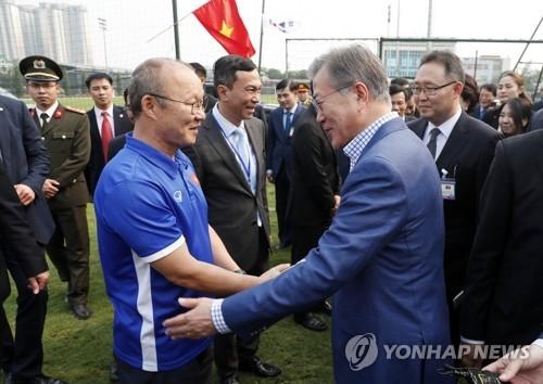 3月22日,在越南河内,韩国总统文在寅(右)看望越南国足的韩国籍主教练朴恒绪。(韩联社)