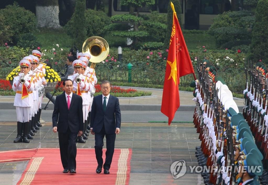 3月23日上午,在河内,正在对越南进行国事访问的韩国总统文在寅(右)同越南国家主席陈大光一同检阅仪仗队。(韩联社)