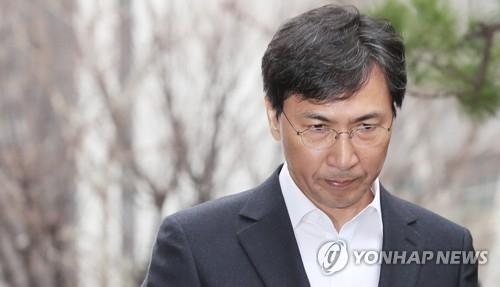 资料图片:3月19日上午,在首尔西部地方检察厅,到案的安熙正神情凝重。(韩联社)
