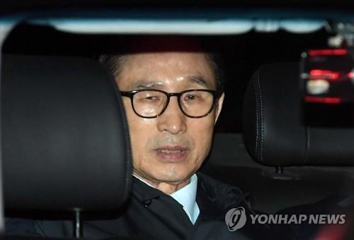 3月23日,在首尔市江南区,李明博在家中被捕后,被押上警车。(韩联社)