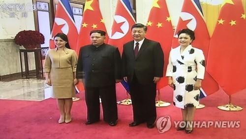 据中国中央电视台(CCTV)3月28日报道,应中国国家主席习近平的邀请,朝鲜劳动党委员长金正恩于3月25日至28日访华。这是习近平和夫人彭丽媛在人民大会堂同金正恩(左二)和夫人李雪主(左一)合影。(韩联社/CCTV截图)