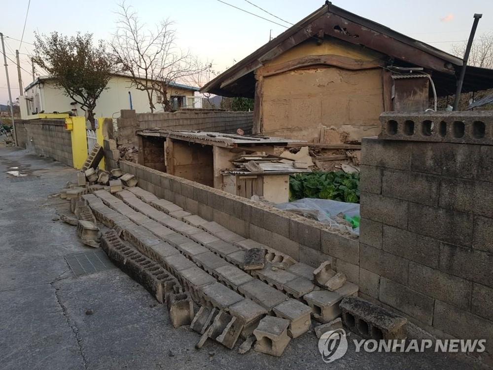资料图片:浦项地震中一民宅外墙被震倒。(韩联社)