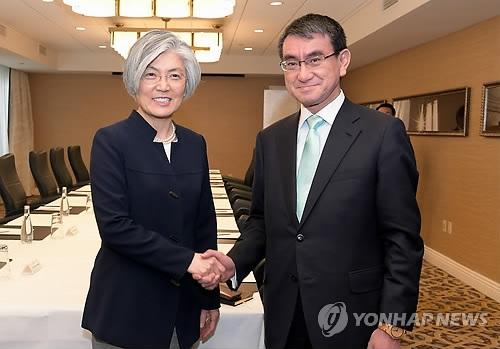 资料图片:当地时间3月17日,在华盛顿,韩国外长康京和(左)与日本外务大臣河野太郎握手。(韩联社/外交部提供)