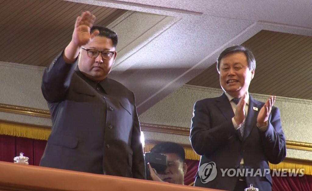 4月1日下午,在平壤市东平壤大剧场,朝鲜劳动党委员长金正恩(左)进场后向观众挥手致意,右为韩国文化体育观光部长官都钟焕。(韩联社/联合采访团电视画面截图)
