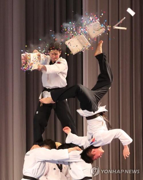 """4月2日下午,在平壤大剧场,韩国跆拳道示范团正在演出中展示""""击破神功""""。(韩联社)"""
