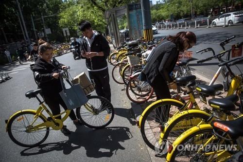 资料图片:市民使用共享单车。(韩联社)