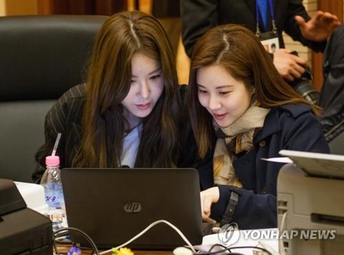 4月2日下午,在平壤市高丽酒店新闻中心,随韩国艺术团访朝的徐贤(右)在上网看新闻。(韩联社)