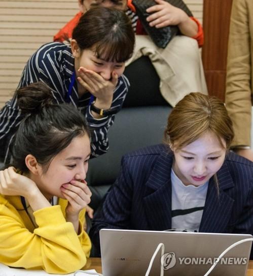 4月2日下午,在平壤市高丽酒店新闻中心,随韩国艺术团访朝的女团组合Red Velvet成员在上网看新闻。(韩联社)