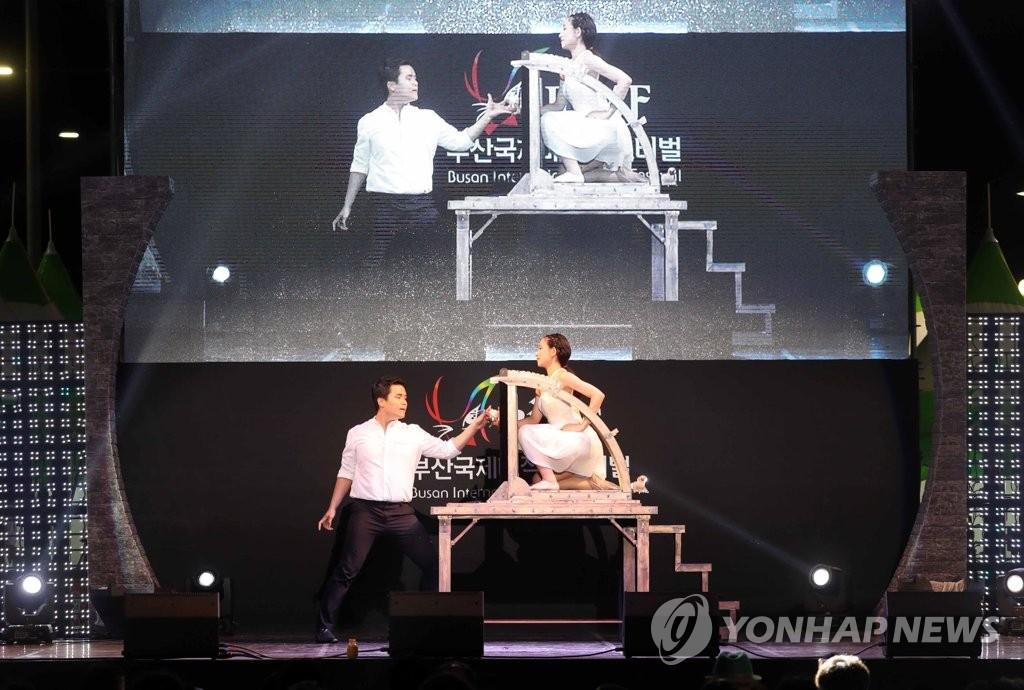 资料图片:8月3日,在釜山海云台海水浴场,参加釜山国际魔术庆典的魔术师正在展示魔术技艺。(韩联社)