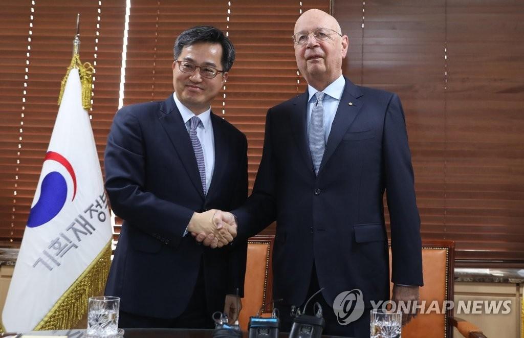 4月10日下午,在韩国中央政府首尔办公大楼,韩国副总理兼企划财政部长官金东兖(左)同世界经济论坛主席施瓦布握手合影。(韩联社)