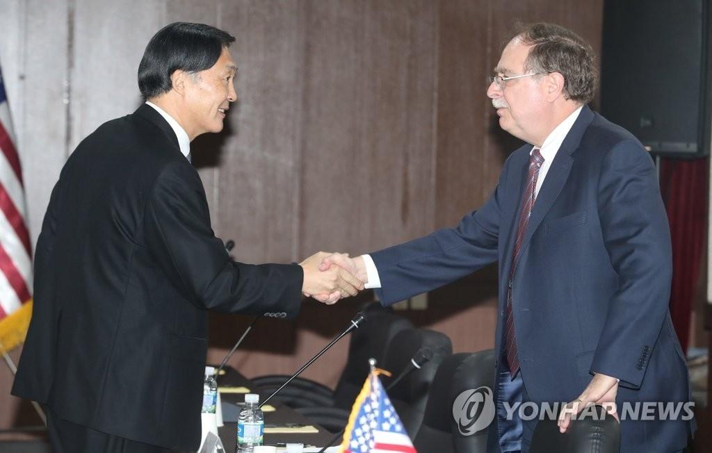 4月11日上午,韩美第10次防卫费分担第二轮谈判在济州国际和平中心启动。会议前,韩方代表张元三(左)与美方代表蒂莫西·贝茨握手。(韩联社)
