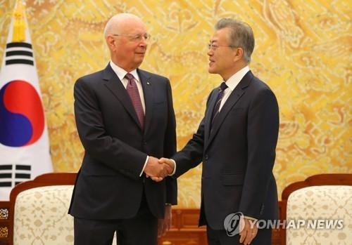 4月11日上午,在青瓦台,韩国总统文在寅(右)同世界经济论坛主席施瓦布握手合影。(韩联社)