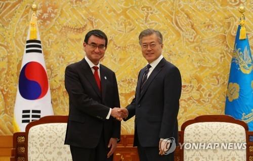 4月11日下午,在韩国青瓦台,总统文在寅(右)接见到访的日本外务大臣河野太郞。图为两人在会晤前握手合影。(韩联社)