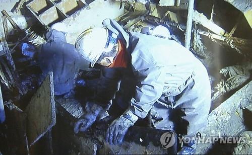 """资料图片:2017年4月21日,""""世越""""号船内搜寻工作的视频对外发布,船体内部满是淤泥,搜寻人员在进行作业。(韩联社)"""