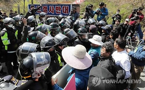"""4月12日,在庆尚北道星州郡""""萨德""""基地入口不远处,当地居民与警方对峙。(韩联社)"""
