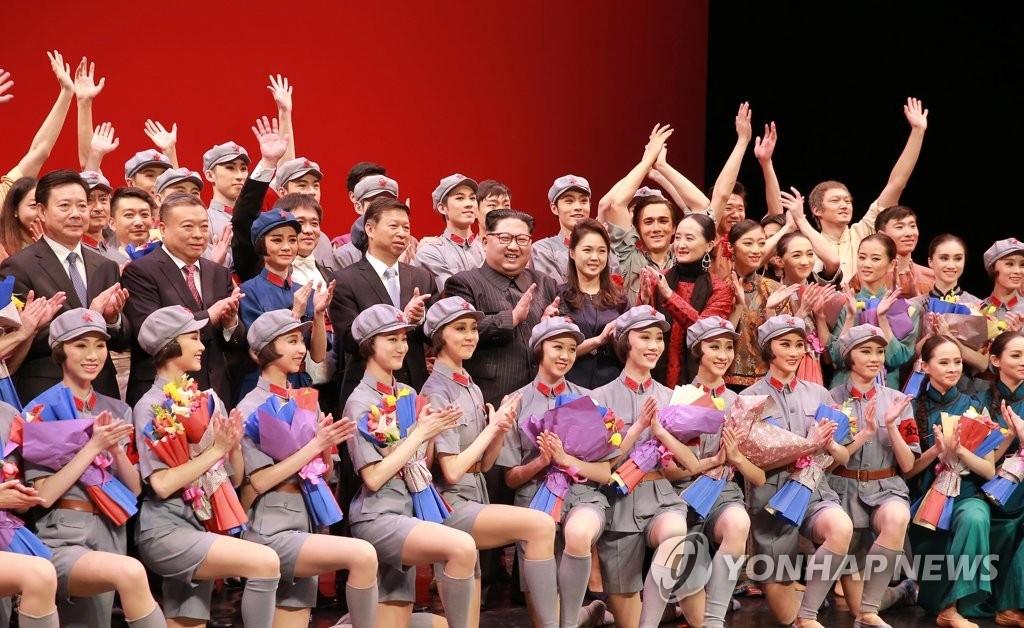 4月16日,在东平壤大剧场,朝鲜劳动党委员长金正恩(第二排左五)和夫人李雪主(第二排左六)观看中国艺术团演出的芭蕾舞剧。图为金正恩夫妇与演职人员合影留念。图片仅限韩国国内使用,严禁转载复制。(韩联社/朝中社)