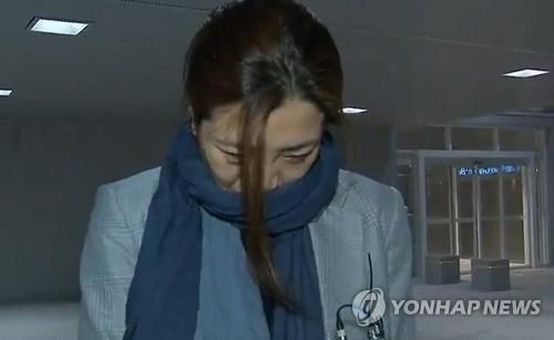 资料图片:4月15日凌晨,在仁川机场,赵显旼走下从岘港起飞的大韩航空K464航班,面对媒体低头问答。(韩联社/MBC电视节目画面截图)