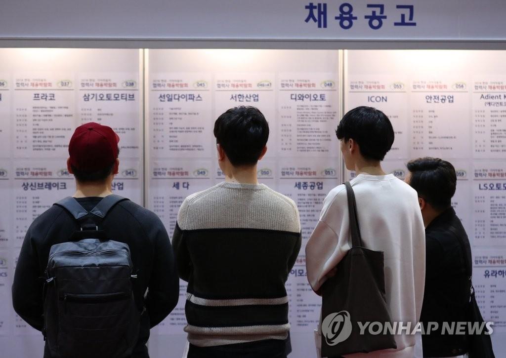 资料图片:4月2日上午,在首尔COEX会展中心举行的现代起亚汽车合作公司招聘博览会上,求职者正在看招聘广告。(韩联社)
