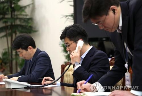 4月20日,在韩国总统府,宋仁培拿起固定电话话筒与朝方人员进行首脑热线试通话。(韩联社)