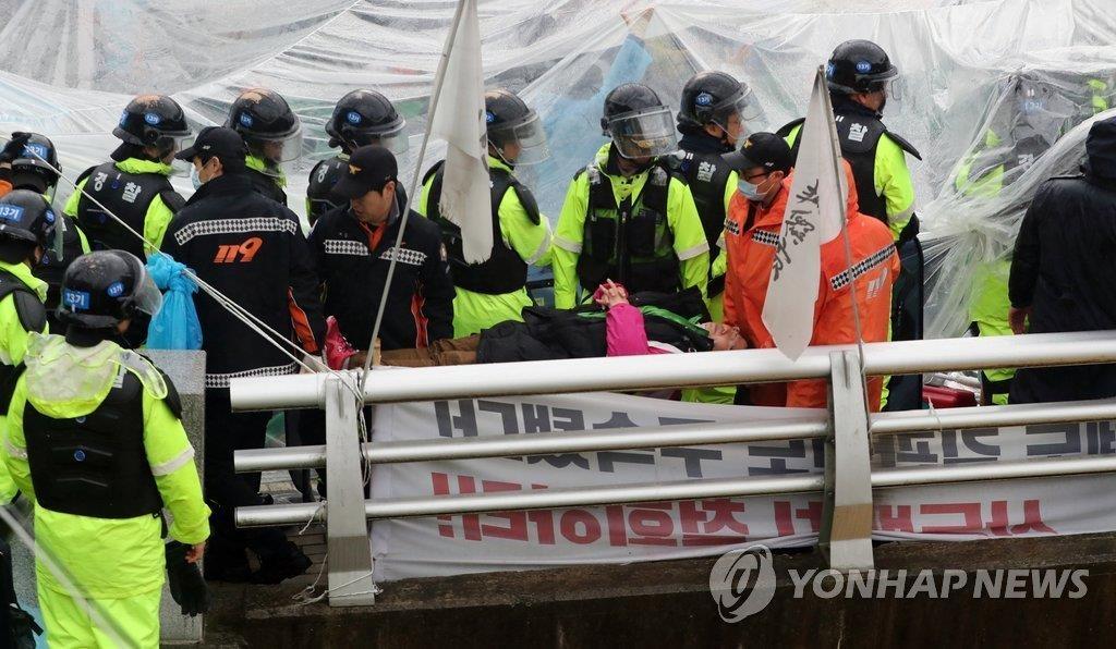 """4月23日上午,在星州郡草田面韶成里萨德基地入口的桥面上,警察正在疏散围堵在""""萨德""""基地入口的居民。(韩联社)"""