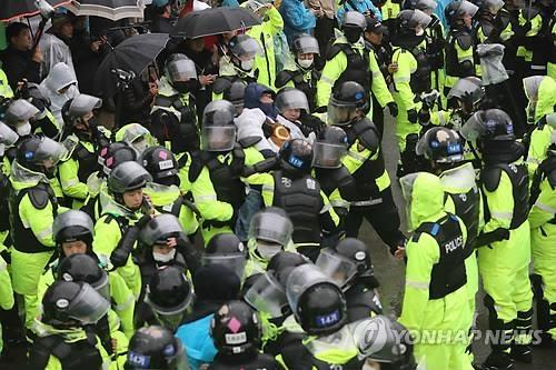 """4月23日上午,在星州郡草田面韶成里,警察正在疏散围堵在""""萨德""""基地入口的居民。(韩联社)"""
