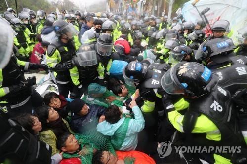 4月23日上午,在星州郡草田面韶成里,警民对峙。(韩联社)
